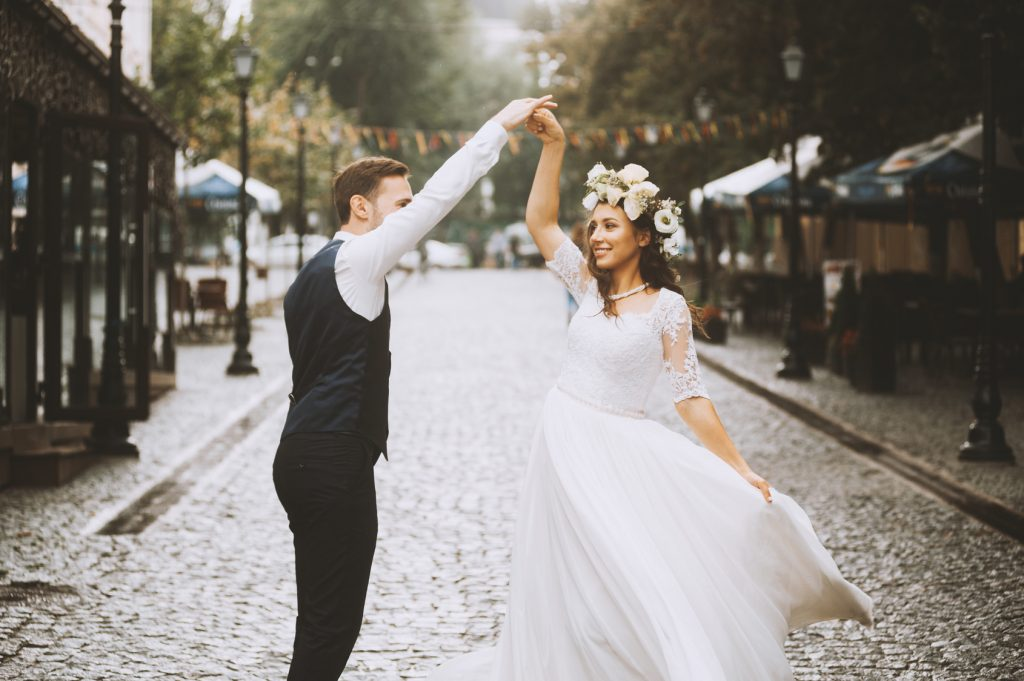 Beautiful newlywed couple is having fun while dancing in the sunny old town street