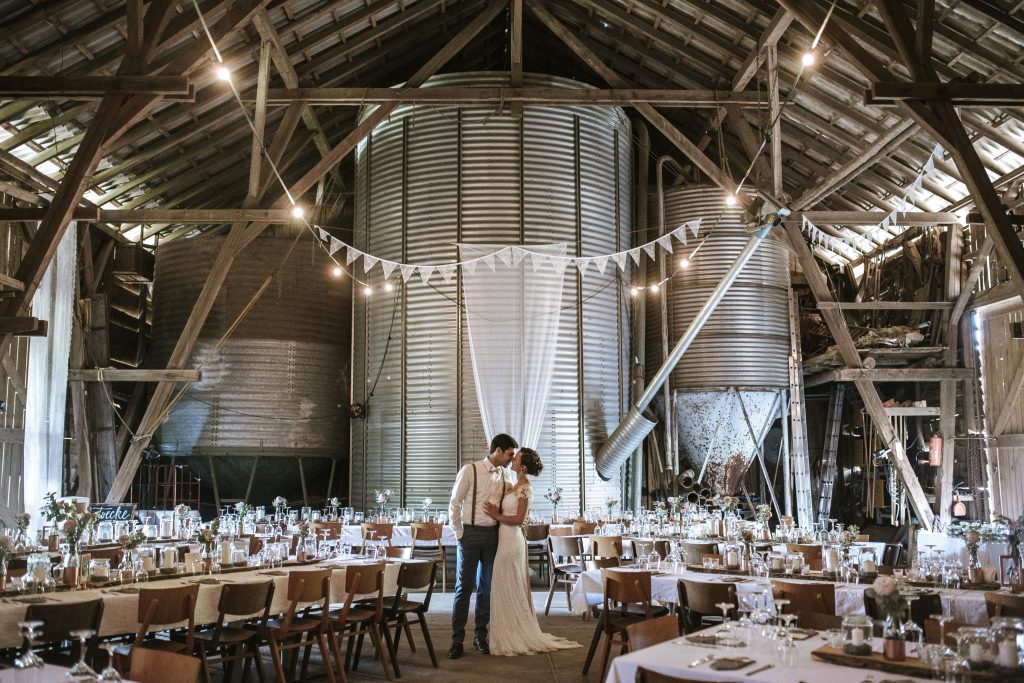 Married Couple kissing in Barn Wedding Location